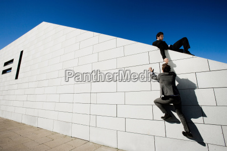 man helping other man over wall