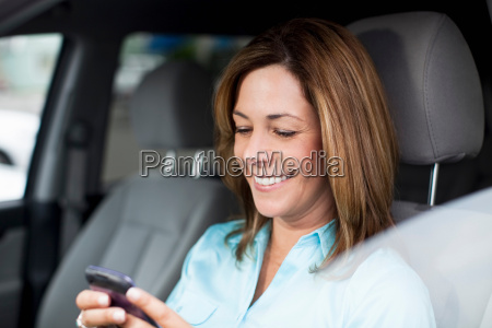woman in car checking cell phone