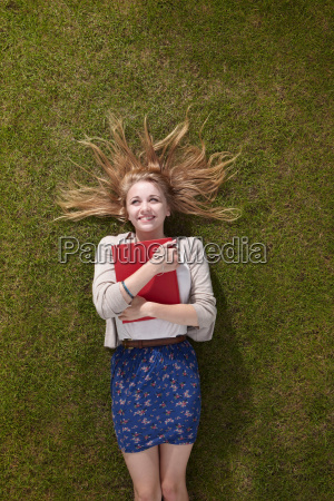 girl lying holding a book