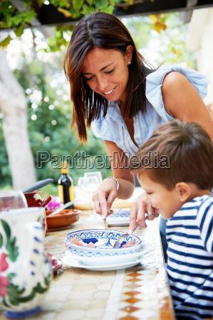 mother serving child some food
