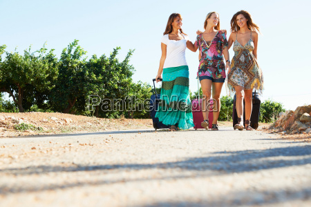 three women with suitcases on the