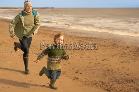 woman young boy running on beach