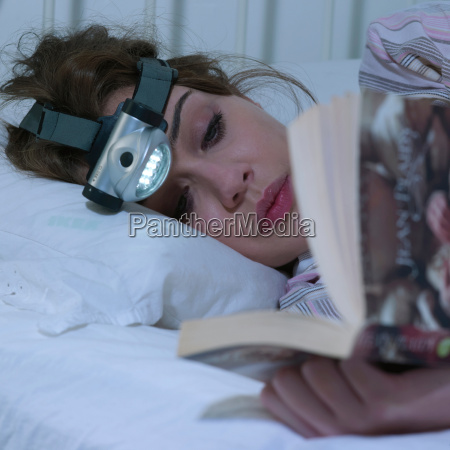 young woman reading with head torch