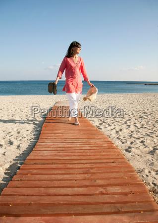 woman walking on boardwalk on beach