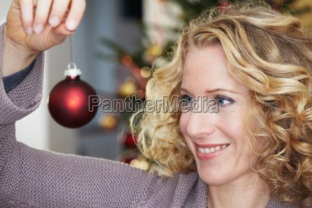 woman looking at christmas ball