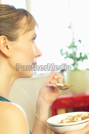 woman eating cereal at home