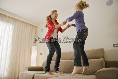 young woman and girl jumping on