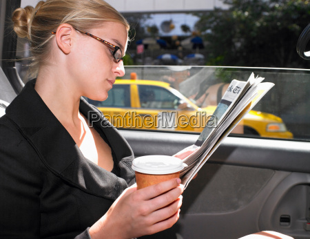 business woman reading news paper in