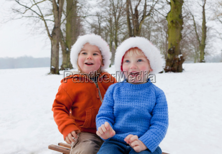 two boys wearing fluffy hats in