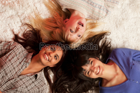 three young women lying on white