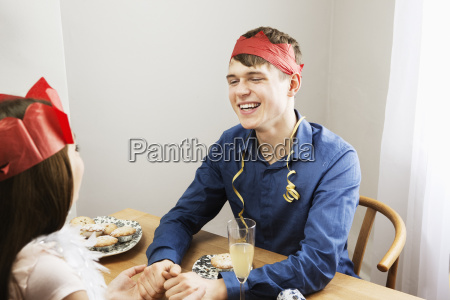 man holding womans hands over table