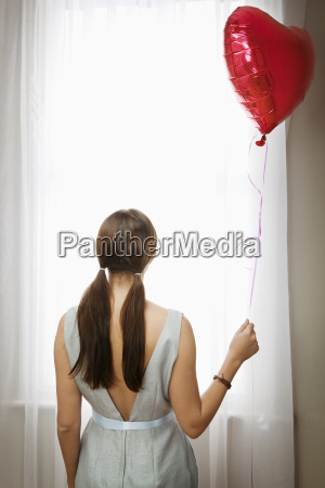 woman holding balloon in front of