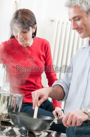 happy couple cooking together at kitchen