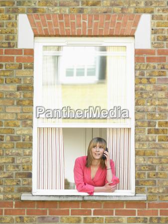 woman talking on phone in window