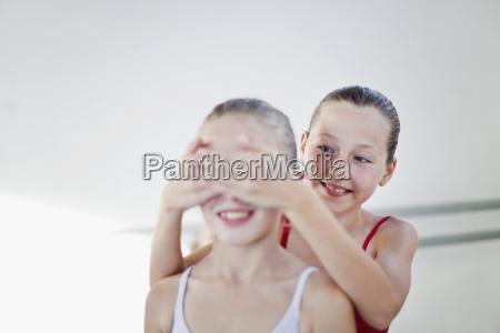 ballet dancer covering friends eyes