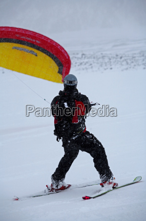 man snow kiting in snow covered