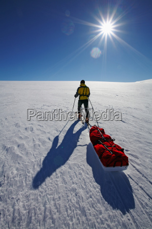 man pulling pack in snow covered