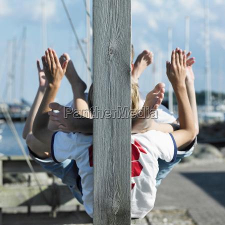 boys sitting together on pier