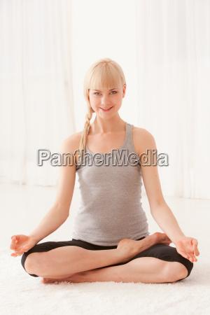 smiling woman meditating cross legged