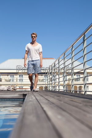 man walking by swimming pool