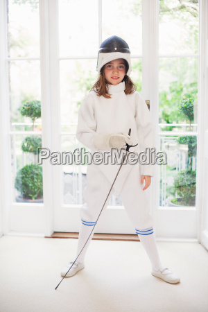 girl wearing fencing gear in living
