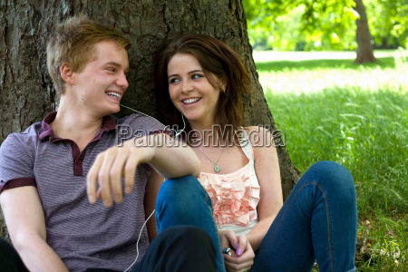teenage couple sitting together in park
