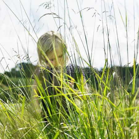 girl hiding behind tall grass