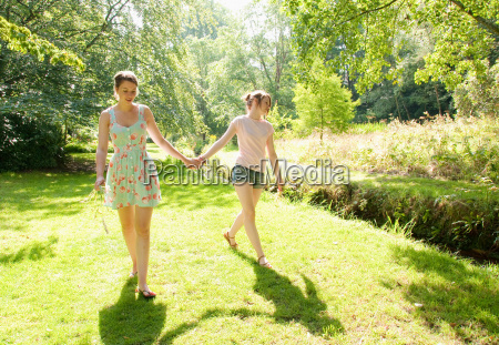 girls walking together by river