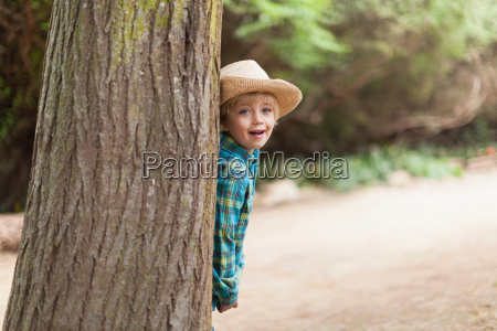 boy wearing cowboy hat behind tree