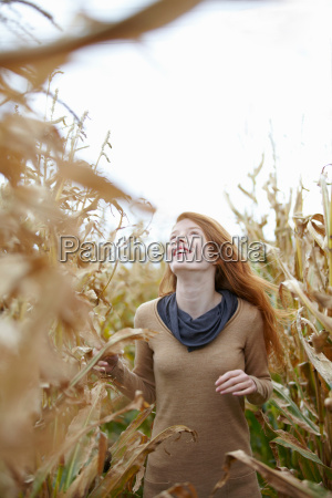 teenage girl walking in cornfield