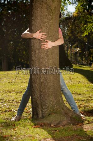 teenage boy hugging tree in park
