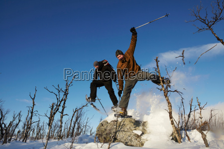 skiers jumping off rock in snow