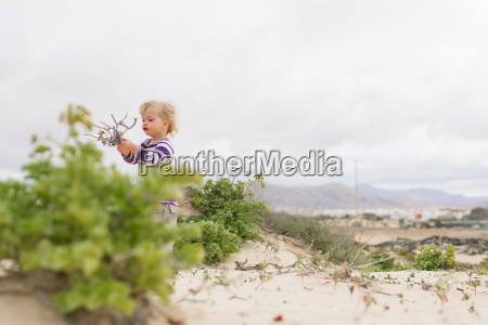 girl playing with twigs on beach
