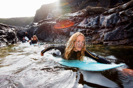 four people lying on surfboards