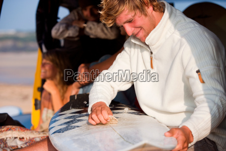 man waxing surfboard with couple smiling