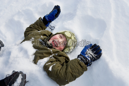 young boy lying in snow