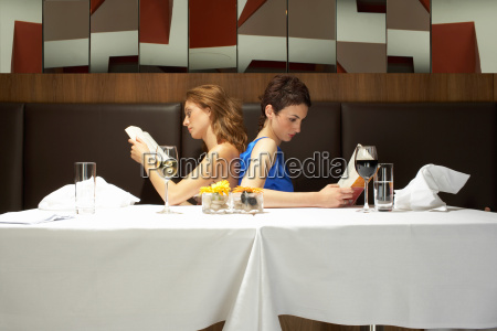 two women in a restaurant reading