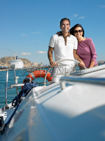 mature couple at wheel of yacht