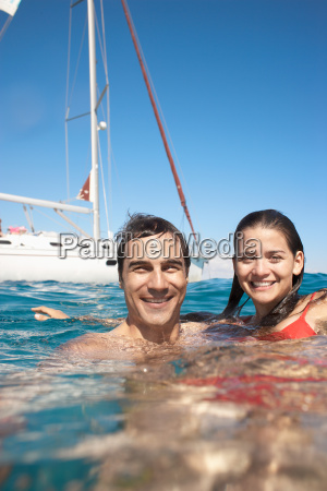 young couple swimming in sea by
