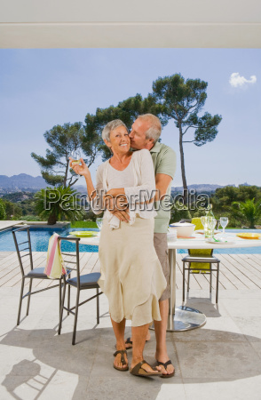 man and woman embracing by poolside