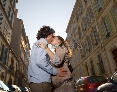 young couple kissing in street