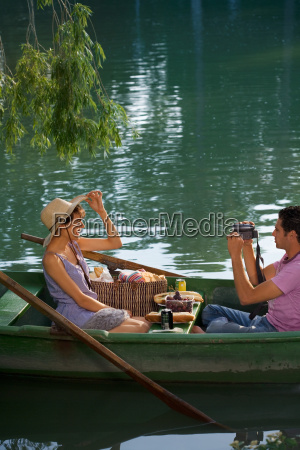 man filming a woman on boat