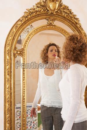 woman applying lipstick in mirror