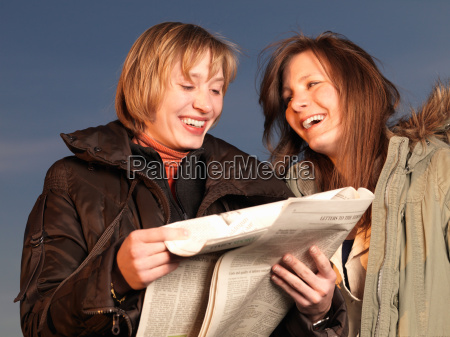 two women reading newspaper laughing