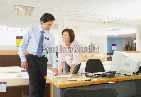 woman signing paperwork with salesman