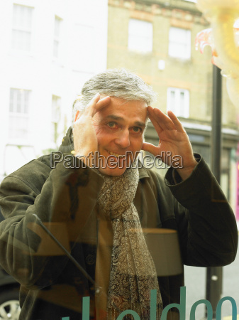 mature man peering into shop window