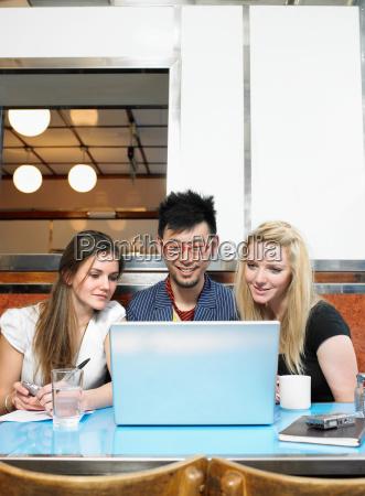 three people looking at laptop