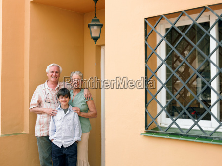 boy standing with grandparents