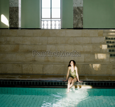 woman sitting by swimming pool