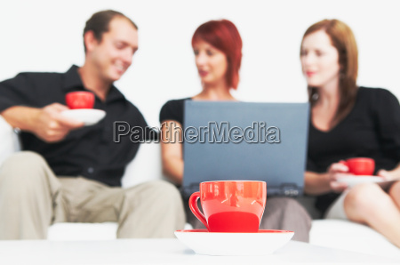 three people talking with hot drink